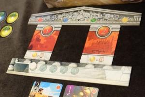 A deux joueurs, on dispose deux cartes de quêtes (une entre l'icône rouge et la bleue, l'autre entre la verte et la jaune). En-dessous, on a placé le marqueur d'époque sur la case 1 (sur les 5 que comportera la partie).
