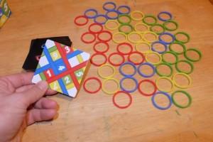 L'idée est toute simple : une carte est retournée avec des numéros sur des zones colorées et il faut empiler sur son pouce les anneaux dans l'ordre avec la bonne couleur. Le premier qui y parvient gagne la carte et ça continue jusqu'à ce que l'un des joueurs en ait obtenu 7. C'est tout !