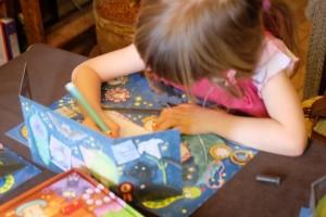 Sur cette photo, Leila essaie de réaliser un dessin le plus fidèle possible à celui de sa carte. Elle cumule plusieurs difficultés pour son âge : reproduire selon un modèle, en temps limité (on lui octroie deux sabliers au lieu d'un) et, cerise sur le gâteau, sans faire tomber le paravent !