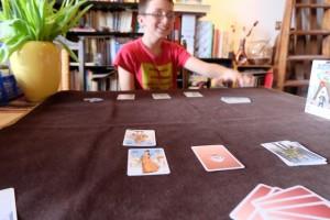 La partie se poursuit et je couine à nouveau : lors de son deuxième tour, Tristan attaque une autre de mes planques avec une carte de valeur 5 et, bingo, il tombe pile poil sur ma carte de valeur 5 !!! Oui, il jubile le gone...