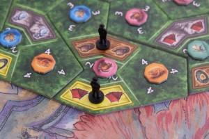 Lorsque je place mon second explorateur noir sur la zone jaune avec la tente, je peux m'adjuger la tuile animal du centre (un fossa géant sur fond rose) et la récupérer. Ce faisant, je score aussi 2PV comme indiqué sur la case...