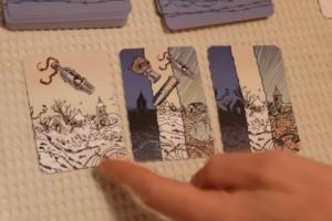 Venons-en au jeu. Nous avons affaire à un jeu coopératif historique, dans lequel nous serons plus confrontés à des dilemmes liés à l'amitié plutôt qu'aux combats proprement dits. Le principe est très simple mais très déroutant : on doit jouer des cartes épreuves de sa main, une à une, sans jamais que trois cartes comportent trois symboles de menaces identiques. Ici, Quentin a joué la dernière carte à droite, trop spontanément, ce qui nous fait rater notre première mission puisque trois symboles de neige sont visibles...