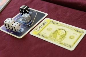 Oh le joli billet de 100 000 $ ! Pour le moment, le joueur blanc (Jean-Luc) mène par 3 dés présents contre 2 au joueur noir (Michel) et 1 au joueur gris (Tristan). Mais avec un dé violet, je vous laisse juste imaginer ce qui pourrait se passer...