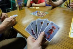 Le jeu se déroule en 5 manche de 5 rounds, sachant qu'au début de chacun on prend une main de 5 cartes. Celles-ci ont une valeur positive ou négative, qui sera affectée à l'un ou l'autre des pions des joueurs sur la piste central. Ici, par exemple, ma main est composée d'une carte de -2, d'une carte de -1, de deux cartes de +1 et d'une carte de +3. Nous appliquons la variante dite stratégique, celle où on est censé contrôler plus de choses...