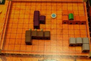 Comme souvent dans ce jeu, on commence à s'observer, posant deux bâtiments de deux couleurs différentes, puis encore deux, ... jusqu'à ce que, forcément, l'un de nous craque et s'adjuge un palais ! C'est mon cas en premier, donc, avec l'acquisition de ce palais orange de taille 6 et que je juge bien intéressant : il me rapportera 4PV pour sa position par rapport au puits et touche déjà le bord droit du plateau. En plus, avec 16 blocs par couleur distribués, je sais qu'il n'en reste plus que 10 et que, surtout, je pourrai toujours utiliser un toit neutre au cas où un gros palais orange se formait...