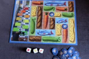 Une fois les 3 dés placés, ou après avoir choisi d'arrêter, le joueur actif les remplace par des jetons de souris : ils symbolisent des portions de nourriture définitivement acquis par les souris (les joueurs donc). Puis, ensuite, le chat avance d'une case (le cas ici), sauf si au moins un aliment a été complété. Vous commencez à voir venir un peu de tactique ? Nous aussi...