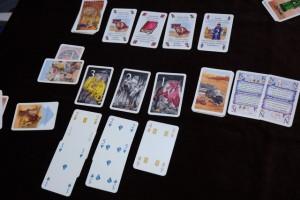 Sur la table, à 3 joueurs, sont étalées 3 cartes de cavernes de dragons avec, en-dessous 3 cartes, puis 2 cartes puis 1 carte avec des trésors indiqués. Sur la droite, on trouve la tente du Djinn avec deux cartes de sorts. Sur la gauche, on trouve le caravanserail. Au-dessus, on a placé une carte de trésor à l'envers sur le +1 (représentant le garde à combattre pour rentrer dans le palais). Enfin, tout en haut, on a installé 4 salles du palais (il y en a 3 ou 4 à chaque tour) avec un objet magique par salle. N'est-on pas incroyablement dans le même jeu que le Morgeland classique ? Surtout si l'on fait fi du plateau et du matos magnifique de la boîte originelle...
