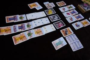 Fin du premier tour, avec les cartes posées par chaque joueur. On passe donc en phase de révélation des cartes, lieu par lieu, en commençant par les cavernes de dragons. L'idée est d'amasser des trésors en bas, pour les dépenser dans les salles du palais, en haut, afin de collecter des objets magiques, sources de 1 PV par objet et d'un pouvoir qui peut être utile... Les sensations sont aussi bonnes que dans le jeu de plateau, mais c'est juste un peu moins tactile : on a l'impression de jouer à un jeu de plateau sans plateau ! Le truc bien, c'est que ce jeu ne prend aucune place pour être emporté partout...