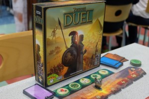 La jolie boîte carrée de Duel avec les non moins jolis composants du jeu au premier plan. A noter la présence d'un goodies magnifique, sous la forme d'un bouclier métallique en remplacement de celui en plastique pour mesurer le niveau militaire des deux joueurs...