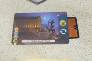 Je construis la première merveille de cette partie, sous la forme du Temple d'Arthémis, en montrant que j'ai les symboles appropriés (au pire, on paie 2 pièces à la banque pour tout symbole non possédé, ou 3 si l'adversaire en a un sur l'une de ses cartes). J'obtiens une petite fortune (12 pièces) + je rejoue ! Nickel...