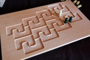 Le plateau est carré, comme je m'amuse à le répéter à chaque fois que je fais une démonstration du jeu : ben oui, 4 zones de chaque côté ! Le but est de relier deux bords opposés du plateau avec ses plaques, sachant que, d'abord, on place ses pions et qu'il en faut trois, par zone pour se l'adjuger. A noter que, si l'adversaire  avait un ou deux pions aussi, il fallait le dédommager en retirant ses propres pions pour les remplacer par les siens. Ci-dessus, voici l'ouverture de notre partie de ce soir, avec Tristan en premier joueur qui a positionné un seul pion jaune et moi deux pions verts...