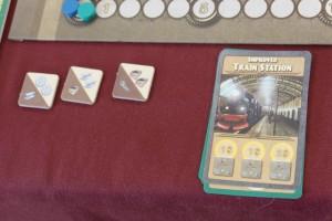A son tour, le joueur actif joue une carte, en applique l'effet, puis c'est au joueur suivant. Limpide ! Ici, par exemple, je joue la carte gare améliorée, sachant qu'au tour d'avant j'avais placé dans mon Labo la technologie qui me le permettait. Avec cette carte, je peux acheter les ressources moins cher : 4$ en tout pour 3 tuiles au lieu de 6$. Sur le long terme, ça peut être pas mal...