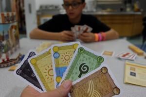 Petite vue de ma main de cartes, avec une carte noire (explorateur) laquelle est une sorte de joker (remplaçant n'importe quel symbole) qui fait avancer le bateau. Quel côté hyper artificiel et hyper hasardeux ! Parmi les autres points plus qu'obscurs, il y a le nombre de cartes piochées par tour et la taille maximale ou non de la main... Aïe aïe aïe :-(