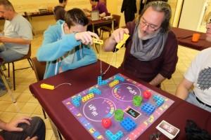 Comme nous sommes 6 à jouer, nous nous mettons par équipes de 2, les associations ainsi créées nous semblant d'autant plus intéressantes : Axel avec Pierre (pion rouge), Romain avec Julie (pion bleu) et Yannick et moi-même (pion vert). Le principe du jeu est de réussir à construire des figures se trouvant sur une carte piochée en un temps limité (enfin, tant que les duels ne sont pas arrivés)...
