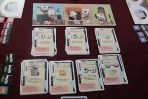 Au centre de la table, on a placé le plateau collectif, lequel est composé de trois zones : le garage (qui proposera des roues et des hélices), le magasin (avec des appareils photos et des filets) et l'armurerie (avec, sans surprise, des armures). Dans chaque lieu, figurent autant d'objets de chaque type que de joueurs. En-dessous, on a positionné les cartes actions disponibles : 9 de garage, magasin et armurerie (à 4 joueurs), puis déchets, publicité, échange et déplacement. Dans chaque pile, les cartes sont strictement identiques. Ce sont ces cartes, qu'on amassera sur la table qui devront être réutilisées dans le même ordre à chacun des trois journées que comporte la partie... Ca va commencer à piquer au niveau des explications...