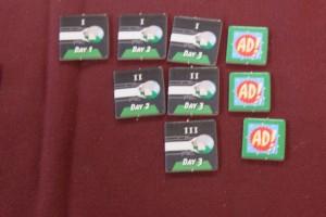 Chaque joueur possède devant lui ses jetons symbolisant ses machines à voyager dans le temps qui sont envoyées dans le passé : on en a 1 pour le jour 1, 2 pour le joueur 2 et 3 pour le jour 3. L'idée est que le premier jour, on va prendre 3 cartes et envoyer une machine dans le temps. Le deuxième jour, on rejouera les 3 mêmes cartes assorties de 3 nouvelles (lesquelles pourront s'intercaler dans l'ordre immuable du premier jour) pour envoyer jusqu'à deux machines dans le temps. Le troisième jour, on rejouera les 6 premières cartes accompagnées de 3 nouvelles (encore une fois intercalables) afin d'envoyer trois machines dans le temps au maximum. Vous voyez la finesse du truc ? Sur la droite, les 3 jetons de publicité sur lesquels je reviendrai...