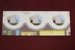 """Mon plateau individuel : il représente mes trois machines utilisables avec autour de chaque """"globe"""" les objets qui seront placés. Sur la gauche, ma première machine sera utilisable à chacun des trois jours, au milieu la seconde qui sera utilisable aux jours 1 et 2, et à droite, la dernière, utilisable uniquement lors du troisième jour. En-dessous, on positionne les éventuelles pénalités reçues : - 1 point par déchet (objet non requis sur une destination), 3 points pour une publicité non suivie d'un voyage et les jetons de failles spatiotemporelles (- 1 point pour un, - 3 points pour deux, - 6 points pour trois, élimination au-dessus !). Oui, ça va piquer..."""