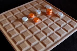 Je viens de fabriquer ma première pile orange ! Et je découvre que fabriquer une pile crée de nouveaux trous sur le plateau, sur lesquels l'adversaire peut rejouer... Je trouve aussi que les pions de Tristan sont clairement espacés et je m'en étonne...