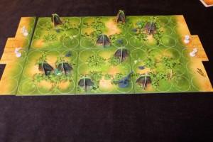 Raptor est donc un jeu asymétrique pour deux joueurs exclusivement, où l'un de nous, Tristan en l'occurrence, jouera les scientifiques, l'autre, moi forcément, incarnera la famille raptor. Le but des scientifiques est de capturer 3 bébés raptors ou d'anéantir la mère (en lui envoyant 5 balles de sommeil). Le but des raptors est de faire s'enfuir 3 bébés ou de nettoyer la jungle de tous les scientifiques. Le plateau est modulaire, biface et les rochers sont placés sur des espaces sans cases circulaires dessous. La mise en place est faite...