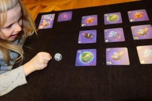 Leila s'amuse comme une petite folle à projeter le dé au centre de la table. Et notez qu'elle a parfaitement saisi que, selon le positionnement des faces du dé, elle n'obtiendra pas la même face sur le dessus une fois le lancer effectué !