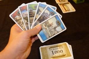 Petite vue de ma main de cartes en début de partie. Le plus intéressant, en fait, c'est que les mêmes cartes ont trois manières d'être jouées : soit en tant que passagers (placées donc en ligne en phase1), soit en tant que gares (placées en colonnes devant soi en respectant un ordre croissant des valeurs), soit en tant qu'argent (en les rajoutant à sa pile, sachant que le dos des cartes indique 1000 marks). Les dilemmes sont donc nombreux...