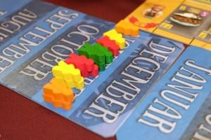 L'originalité du jeu tient dans ce calendrier où sont placés des meeples aux couleurs des joueurs : les jaunes pour Tristan, les rouges pour Jean-Luc, les verts pour Jacques et les orange pour moi. A noter qu'ils sont soit de sexe féminin soit de sexe masculin et que, s'ils sont empilés, ils sont considérés comme des meeples plus forts.