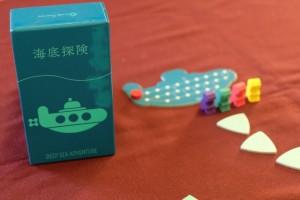 Magnifique petit jeu dans une boîte minimaliste mais avec un matériel relativement abondant quand même ! Qui nous accompagnera au fond des mers ?