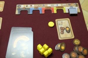Devant soi, chacun dispose d'un support représentant ses possessions en briques noires (coût de 1), bleues (coût de 2), rouges (coût de 3), jaunes (coût de 4) et blanches (coût de 5). On peut voir que j'ai investi dans une brique blanche pour le moment grâce à une action de ma carte jouée précédemment et en fonction de la position de mon pion au milieu du plateau central.