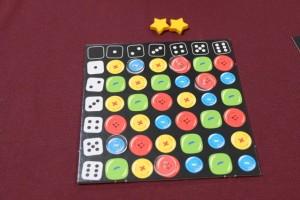 Mes boutons blancs transparents recouvrent 5 cases de mon plateau, dont 3 fois un bouton rouge. Comme je m'étais retiré à temps, je vais placer deux étoiles...