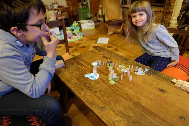 Le jeu est coopératif et nous y jouons à trois : Tristan la grimace et Leila la souriante, accompagnant votre serviteur photographe. Nous avons deux fois 10 minutes pour placer des dominos sur la table, lesquels vont nous permettre de relier des disques de terrain entre eux, pour que les animaux (jetons ronds) et les paysages (jetons rectangulaires) correspondent.