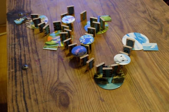 Voici ce que nous avons réussi à faire lors de la première manche de 10 minutes. Ce n'est pas franchement pas beaucoup en regard du nombre de dominos que nous avons chacun à placer (52 !!!). Nous avons du mal à bien intégrer les règles : que doit-on vraiment relier entre eux ? Quelle tolérance avons-nous en terme de dominos qui ne sont pas du même type ? Où sont les entrées et sorties d'eau sur certains disques de terrain ? Sans compter que, selon où l'on se trouve autour de la table, on ne voit pas très bien le type de domino... Très difficile, en tout cas, au contraire de ce que j'avais pu trouver sur internet, où j'avais lu qu'à 6 ans on pouvait y jouer sans problème...
