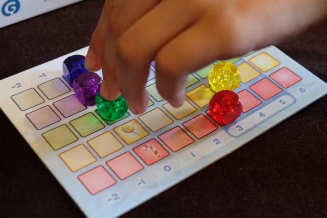 """Les cubes avancent les uns après les autres, enfin surtout le jaune (par Tristan) et le rouge (par moi). Ici, il s'apprête à déplacer le vert. A noter que le dé qui fait progresser les cubes possèdent des valeurs positives comme négatives. Enfin, sachez que la partie s'achèvera dès lors qu'un cube aura atteint la colonne marquée """"G"""" à droite (mais il faut au moins un autre cube dans la zone 3, 4, 5 pour qu'on puisse le faire arriver)."""