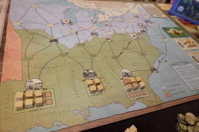 Premiers éléments du jeu : la zone des plantations du sud des Etats-Unis. Ci-dessus, vous y voyez trois plantations, la première pouvant accueillir 8 esclaves (cubes beiges) avec 6 présents, la seconde avec 4 places et 4 présents, la troisième avec 9 places et 6 présents. Le but du jeu est de faire fuir ces esclaves vers le Canada (le paradis de la liberté en quelque sorte). Pour cela, il va falloir emprunter les routes tracées sur le plateau en se méfiant des chasseurs d'esclaves (jetons avec symbole coloré) qui auraient tôt fait de les ramener aux marchés des esclaves...