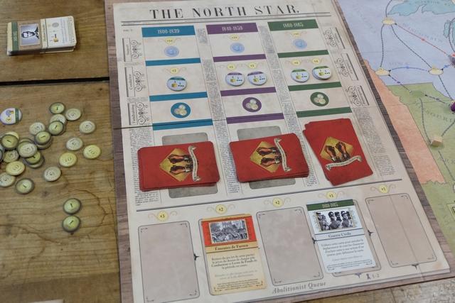 La zone des cartes sur le plateau, avec la seconde carte rouge que nous avons en jeu ! Absolument phénoménal comme hasard : seulement 2 cartes rouges en tout sur les 10 qui se trouvaient dans les pioches ! Forcément, cela a rendu le jeu très (trop) facile, mais ce n'est pas vraiment la faute au jeu...