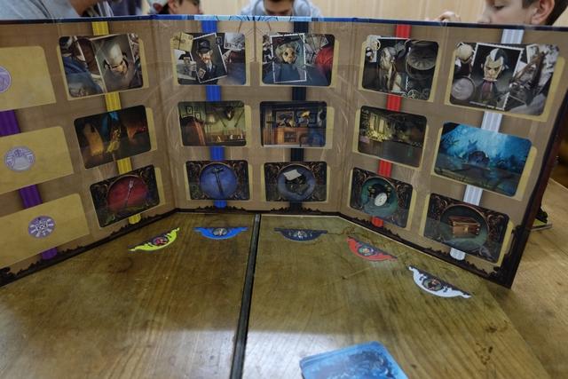 Incarnant le fantôme, je dispose d'un paravent absolument fantastique : doté de six colonnes (une par joueur en dehors du fantôme) et de trois lignes (une par critère : personnage, lieu, objet). Au début de la partie, j'affecte aléatoirement un personnage, un lieu et un objet par joueur, en glissant les cartes sous la bande de plastique transparent (quelle idée géniale !). Je place au milieu de la table les mêmes cartes + 1  de chaque type (niveau facile) afin que les joueurs voient quels éléments sont utilisés pour cette partie. Enfin, derrière mon paravent, je place un marqueur en-dessous de chaque colonne afin de m'aider pour organiser ma remise de cartes de vision à venir...