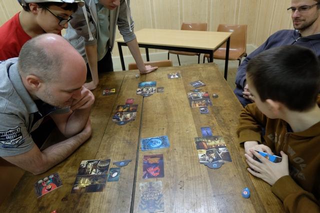 Pour cette phase, les joueurs ont sorti leurs 3 cartes de leur étui (personnage, lieu et objet) et les ont étalées sur la table avec un numéro à côté (de 1 à 5). En tant que fantôme, j'ai dû choisir un lot de 3 cartes et trouver 3 cartes de vision depuis ma main qui représente ce lot (une pour le personnage, une pour le lieu et une pour l'objet). Ensuite, j'ai positionné un jeton de culpabilité avec le numéro du lot en question, face cachée, sur la piste de clairvoyance. Ensuite, les trois joueurs avec le moins de clairvoyance ont eu droit à ce que je retourne 2 cartes parmi les 3 afin qu'ils choisissent secrètement le numéro qui leur paraissait le plus probable (secteur glissé dans leur étui). Ensuite, la troisième carte sera retournée pour les deux joueurs restants, pour qu'ils votent aussi.