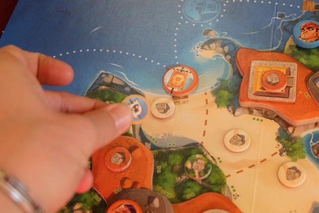 Ayant trouvé un indice de type Drapeau, je place un ponton à notre couleur (orange) sur l'un des pontons du plateau. Cela est très utile en prévision de la fin de partie lorsqu'il s'agira de fuir avec l'amulette...
