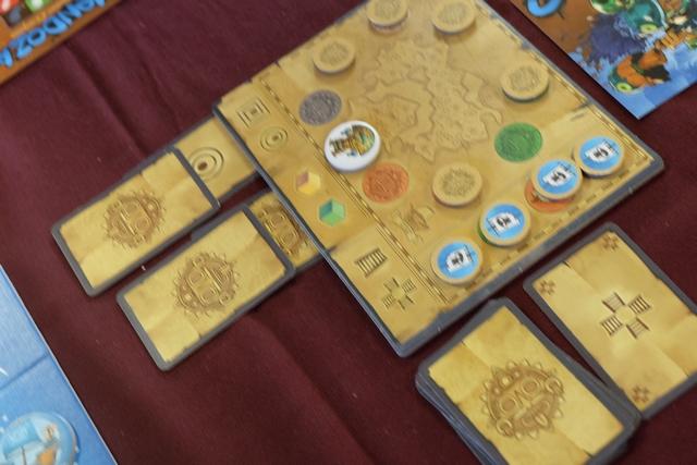J'apprécie vraiment le système de localisation de l'amulette : quand on tombe sur un jeton doré on doit ajouter une carte à l'une des colonnes (soit une de sa main qu'on met face cachée, soit celle de la pioche, ici les 4 escaliers, face visible). Pour le moment, il y a une forme ronde (face visible) et une carte face cachée (placée par Tristan et moi : forme carrée). En cas d'égalité, c'est la dernière posée qui comptera, donc la forme carrée. Pour les couleurs, nous avons mis Or face cachée avant que nos adversaires place probablement vert face cachée aussi. Aucune information sur les escaliers pour le moment. Dès que la 7ème carte sera placée, on révélera le tout et on aura, ainsi, identifié le seul temple possible ! Limpide et malin...