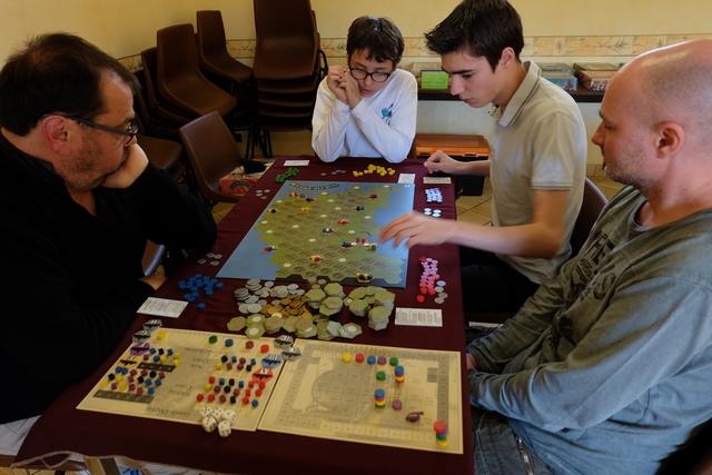 Nous jouons cette partie à 5 joueurs, dont deux vrais débutants : Jean-Luc (à gauche, avec les bleus) et Yannick (à droite, avec les rouges). Quant aux deux autres joueurs, Tristan (avec les jaunes) et Axel (avec les violets), ils n'ont qu'une partie au compteur. A noter quand même qu'Axel l'avait gagnée cette satanée partie... ;-)