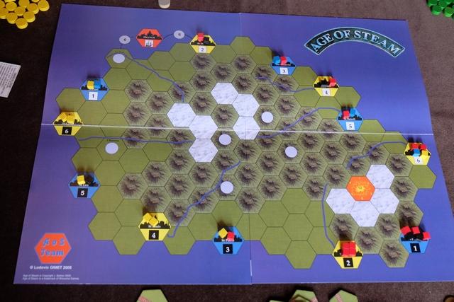 Nous venons d'installer le plateau au centre de la table et Tristan découvre avidement les spécificités de cette carte pour deux joueurs exclusivement : - Les villes ne sont que bleues ou jaunes, plus la France qui est rouge (et non productive) et les 4 villes urbanisables qui sont noires, - Les coûts de construction sont modifiés, tout comme le capital de chaque joueur au départ : 0 $ malgré 2 titres en poche ! - Avant de choisir les actions, le deuxième joueur en bloque puis le premier joueur fait de même (ça va couiner...), sans que l'on puisse bloquer les mêmes à chaque tour, - Le volcan (le Piton de la Fournaise) peut entrer en éruption sur un lancer de 3 dés qui atteint ou dépasse 12, - ...