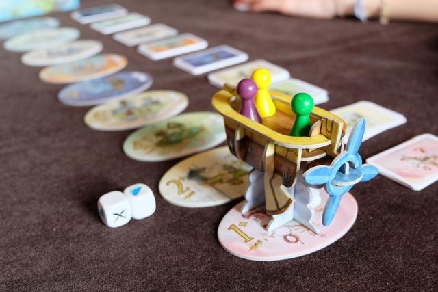 Nous voici embarqués dans une partie à 3 joueurs, Maitena (épaulée par Leila) en violet, Tristan en jaune et moi en vert. Nous sommes placés sur le bateau, sur la première cité, avec votre serviteur en capitaine pour le premier tour de ce premier voyage (je suis installé sur le siège, au fond du vaisseau). La première action du capitaine consiste à jeter autant de dés qu'indiqués sur la cité suivante (donc 2 pour le moment). J'obtiens un dé blanc (pas d'avarie) et un épais brouillard bleu.