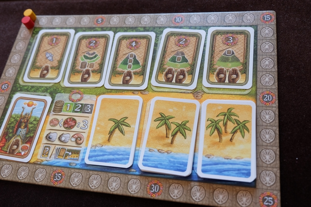 Une partie se joue en deux manches : la première se déroule jusqu'à l'épuisement de la pile de cartes avec deux palmiers, la seconde se poursuit un peu après l'épuisement de la pile de cartes avec trois palmiers. En haut figurent des cartes de décomptes de fin de manches (mais remis en place à la fin du premier) que nous allons acquérir en payant les coquillages indiqués (1 ou 2). A côté des palmiers, première petite vue des éléments pris en compte lors d'un décompte...
