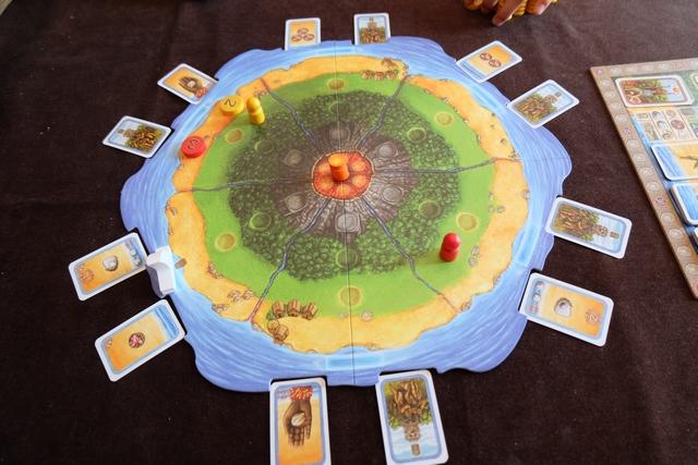 Le matériel est somptueux, c'est très clair ! Alors, je vous présente ci-dessus l'île avec ses six secteurs répartis autour du volcan central, chaque secteur étant divisé en quatre zones : plage, plaine, forêt et montagne. Tout autour, on trouve l'océan avec un bateau qui sillonne le pourtour de l'île en sens horaire. Des cartes (celles avec les palmiers au dos) sont réparties deux par deux au hasard par secteur. Le tour de jeu d'un joueur consiste le plus souvent à poser un jeton numéroté à sa couleur sur un secteur du plateau : soit en dehors de la zone du bateau ce qui lui permet de déplacer son chamane (gros pion) de deux zones maximum avec une seule montée, soit dans la zone du bateau ce qui fait avancer le bateau d'un nombre de secteurs égal à la valeur du jeton (et provoquant une résolution de majorité dans le secteur d'arrivée)...