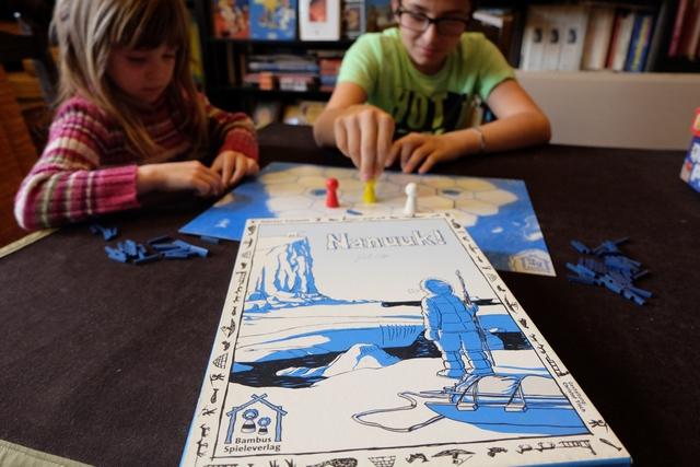 Le jeu Nanuuk ! présente la particularité de proposer plusieurs niveaux de règles, avec plus ou moins de composants, et de permettre même le jeu par équipe ! Nous enchaînerons donc trois parties, dans divers formats, en commençant par la règle dite d'initiation : chaque joueur joue un inuit (rouge pour Leila, jaune pour Leila, blanc pour moi) qui tente de survivre sur la banquise (un mouvement par tour = une fissure)...