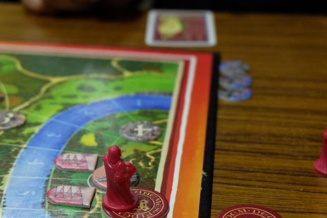 Ayant investi une église dans un duché, Sébastien a ajouté un disque rouge sous son duc pour indiquer qu'il est promu évêque. Ensuite,  comme il est  le seul à l'avoir fait pour le moment, Sébastien récupère la carte archevêque qu'il place devant lui (en haut). Cette carte lui donne le pouvoir de jouer une carte avec numéro pour remplacer un chevalier adverse au lieu de ne jouer que sur les cases vides. Pas mal... Et dommage pour moi car je voulais le faire ! Il va me falloir me battre pour le dépasser sur le nombre d'évêques...