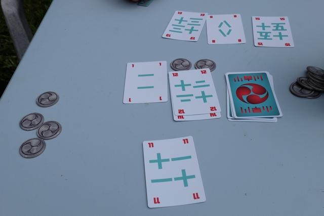 Les cartes 13, 8 et 15 en haut ont écartées par certains des joueurs. Petit exemple de résolution : seuls Tristan et moi avons payé 1 jeton (au centre de la table) et c'est lui qui remporte le pli avec sa carte 1, à laquelle s'ajoute la 12 d'à-côté de la pioche, contre ma carte 11. OK, je crois que tout le monde a compris...