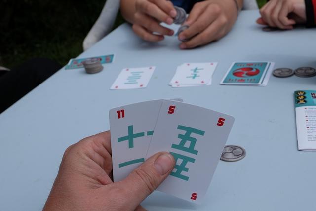 Les choix ne sont jamais évidents. Ci-dessus, que faire avec mes deux cartes ? Laquelle conserver ? Je crois qu'elles sont toutes les deux perdantes, puisque, juste avant, je me suis rendu compte que quelqu'un avait défaussé un 14 ou un 15 (ce qui m'a donné à penser qu'il avait une toute petite carte, donc plus basse que mon 5). De même, si je garde le 11, je ne peux pas espérer grand chose non plus : la carte du centre ajoutée à la plus faible va certainement conduire à un total plus élevé ! Et comme il ne me reste plus qu'un jeton, j'ai tout intérêt à ne pas prendre le risque de me faire éliminer : je ne participerai donc pas à cette manche.