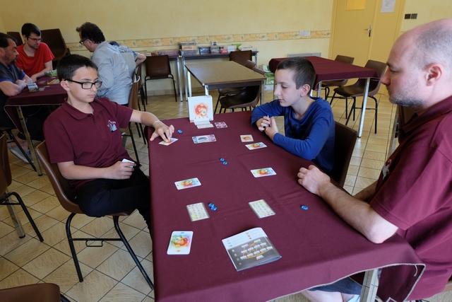 Le premier joueur change à chaque tour (la carte est passée à sa gauche) et c'est maintenant Samuel qui le devient. Va-t-on pouvoir réussir l'enchaînement de coups qu'on avait évoqué au départ pour défausser rapidement les cartes d'agression ? L'idée : celui qui a la carte Les Hécatonchires la joue au plus tôt (donc au 2ème tour), on la laisse en jeu jusqu'à ce que plusieurs cartes de Eclair des Cyclope soient jouées (et donc défaussées). Bon, comme c'est moi qui l'ai, on va voir si Tristan se souvient de cette idée de départ et, par la suite, lorsque Yannick sera 1er joueur, si je peux au moins passer une de mes deux cartes Eclair de Cyclope). Tant pis pour les quelques éléments qui seront perdues en même temps...