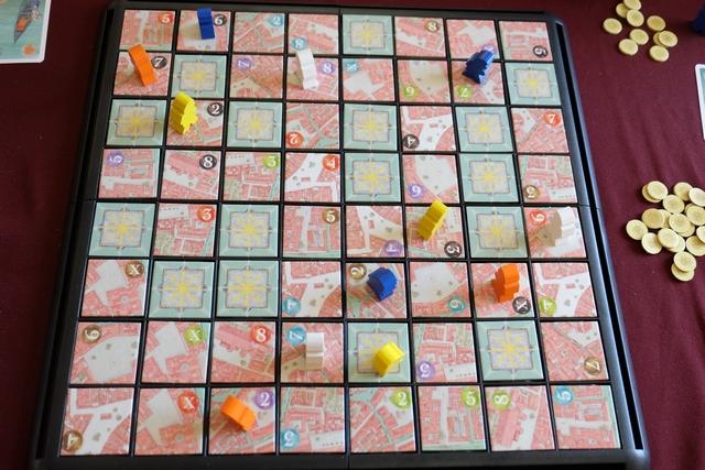 Voici la vue générale en début de partie, après que chaque joueur a placé ses 3 personnages sur des quartiers de valeur différente (les miens, les blancs, sont sur un quartier 7 bleu, 8 violet et 6 rouge). A son tour, le joueur actif PEUT déplacer un de ses personnages d'autant de cases que souhaitées dans une seule direction (non bloquée bien sûr), puis acheter un trésor de la couleur du quartier atteint (le premier coûte 1 sou, le deuxième 2 sous, les troisième 3 sous, ...) et, enfin, il DOIT jouer une carte de sa main et retourner la tuile du quartier concerné.