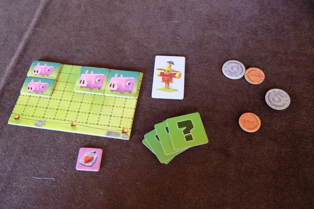 """Chaque joueur est un fermier qui va essayer de développer une exploitation de """"Cochons Contents"""", à partir de son capital de départ (45 sous) et d'un pré initial. En ce qui me concerne, je choisis les 5 actions suivantes pour débuter : achat de deux cochons """"moyens"""" et de deux """"petits"""", ainsi qu'une amulette de naissance (laquelle me permettra, en cas de reproduction de mes adultes, de faire profiter l'un d'eux d'une croissance accrue immédiate : directement """"petit"""" et non """"bébé""""). Mon capital restant est donc de 12 sous. Je suis le premier joueur au premier tour sur les douze que comptera la partie (plaquette blanche avec l'épouvantail)."""